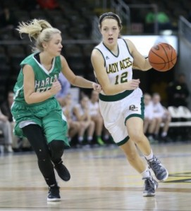 Owensboro Catholic's Emily Marshall drives down the court with Harlan's Jordan Brock defending. (Photo by Jim Osborn)